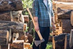 bebouwd beeld van houthakker in geruit overhemd met getatoeeerde handen die bijl tussen logboeken houden bij zaagmolen stock afbeeldingen