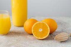 Bebouwd beeld van jus d'orange in glas, drie rijpe sinaasappelen en houten juicer op witte rustieke achtergrond Verse Vruchten Ge royalty-vrije stock afbeeldingen