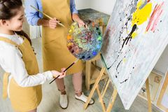 bebouwd beeld van leraar en leerling die verf op palet in workshop kiezen van stock fotografie
