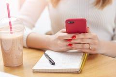Bebouwd beeld van onherkenbare vrouw met rode manicure, die smartphone die in beide handen houden, nota's maken, die rust hebben  stock foto's