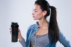 Bebouwd beeld van sporten mooie vrouw met water in studio over witte achtergrond Stock Fotografie