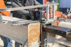 bebouwd beeld van timmerman in beschermende handschoenen die machinezaag gebruiken bij zaagmolen Houten logboek die met kettingza royalty-vrije stock fotografie