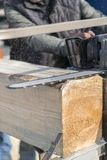 bebouwd beeld van timmerman in beschermende handschoenen die machinezaag gebruiken bij zaagmolen Houten logboek die met kettingza royalty-vrije stock afbeeldingen