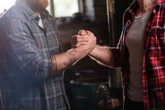 bebouwd beeld van timmerman met getatoeeerde hand het schudden hand van partner bij zaagmolen royalty-vrije stock fotografie