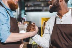 bebouwd beeld van twee glimlachende eigenaars van koffiewinkel het schudden royalty-vrije stock afbeeldingen