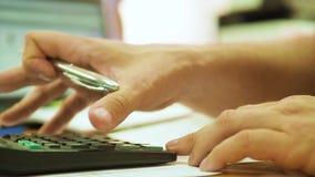 Bebouwd beeld van zakenman die calculator in bureau gebruiken stock footage