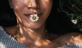 Bebouwd close-up horizontaal schot van donkerbruin jong meisje met madeliefjebloem in mond die in openlucht van aard genieten Por royalty-vrije stock foto