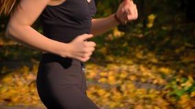 Bebouwd dolly schot van bodem aan schot van jong Kaukasisch meisje in jumpsuit die in herfstpark lopen stock video