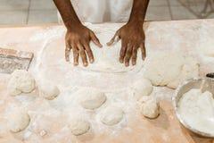 Bebouwd schot van Afrikaans Amerikaans bakker het kneden deeg voor gebakje stock afbeeldingen