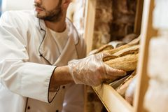 bebouwd schot van bakker die brood van brood op plank zetten royalty-vrije stock afbeeldingen