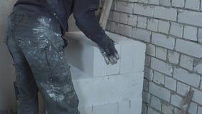Bebouwd schot van bouwer in vuile het werkslijtage die blokken opslaan bij bouwwerf stock videobeelden