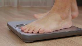 Bebouwd schot van de blootvoetse mens die gewicht controleren op schaal stock video