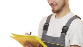 Bebouwd schot van een de industriearbeider die makend nota's over klembord glimlachen stock afbeeldingen