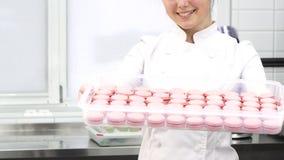 Bebouwd schot van een gebakjechef-kok het glimlachen het standhouden dienblad met roze makarons stock foto