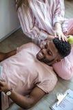 Bebouwd schot van een jonge Afrikaanse Amerikaanse paar het letten op televisie thuis stock foto