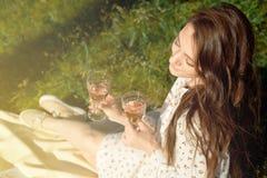 Bebouwd schot van een meisje, in een de zomerkleding, die met een glas wijn bij een picknick zitten terwijl in openlucht het geni stock fotografie