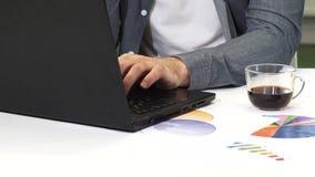 Bebouwd schot van een mens die aan laptop op het kantoor werken stock videobeelden