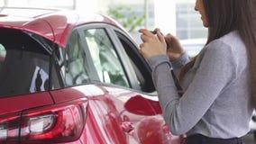 Bebouwd schot van een vrouw die foto's van haar nieuwe auto nemen stock video