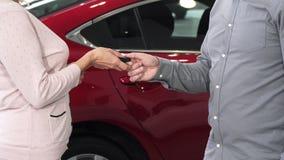 Bebouwd schot van een vrouw die sleutels ontvangen aan haar nieuwe auto bij het handel drijven stock footage