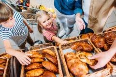 bebouwd schot van gelukkige familie met twee jonge geitjes die gebakjes kiezen stock afbeeldingen