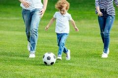 bebouwd schot van jonge ouders met zoons speelvoetbal royalty-vrije stock foto