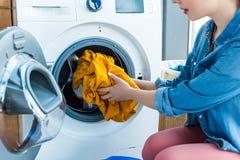 bebouwd schot van jonge vrouw die wasserij zetten in wasmachine stock afbeelding