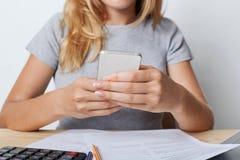 Bebouwd schot van jonge vrouwelijke enterpreneur in grijze T-shirt, houdend slimme telefoon in handen, die voor minuut na adminis Stock Afbeeldingen