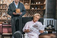 bebouwd schot van man holdingspannekoeken terwijl vrouw in de krant van de robelezing royalty-vrije stock afbeeldingen
