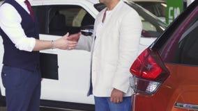 Bebouwd schot van mens het schudden handen met autohandelaar stock videobeelden