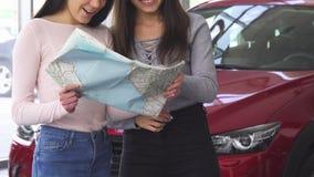 Bebouwd schot van twee gelukkige vrouwelijke vrienden die een kaart voor de auto onderzoeken stock footage