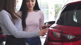 Bebouwd schot van twee vrouwen die auto's kiezen bij het handel drijven stock videobeelden