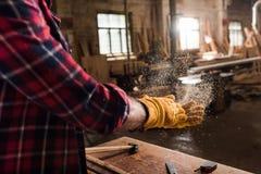 bebouwd schot van vakman in beschermende handschoenen die van houten spaanders van handen schudden stock fotografie