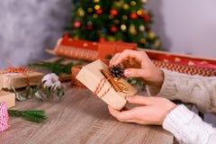 Bebouwd schot van vrouw het voorbereidingen treffen voor Kerstmis, verpakkende hand - gemaakte giftdozen royalty-vrije stock foto