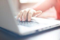 Bebouwd schot van vrouwen` s handen die op toetsenbord die van laptop computer typen, een hoofdstuk van haar boek beëindigen terw royalty-vrije stock afbeelding