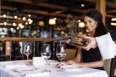 Bebouwde beeldkelner die witte wijn voor glimlachende vrouw gieten stock afbeelding