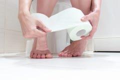 Bebouwde benen die van een vrouw, op een toilet met verminderde damesslipjes en een broodje van toiletpapier in haar hand zitten  royalty-vrije stock fotografie