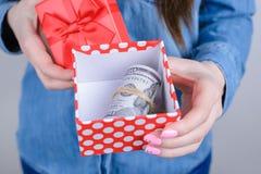 Bebouwde close-upfoto van opgewekte gelukkige zekere bedrijfsonderneemster die pakket met stapelstapel tonen van geldholding in h stock foto