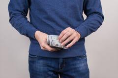 Bebouwde close-upfoto van zekere kerel in blauwe van de de verbindingsdraadholding van de sweatertrui de stapelstapel van geld in royalty-vrije stock afbeelding