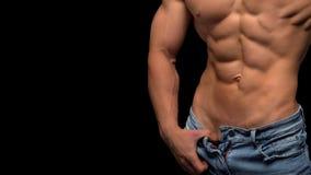 Bebouwde foto van een sportieve mens met spierlichaam in jeans die in studio stellen royalty-vrije stock foto's