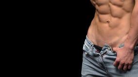 Bebouwde foto van een sportieve mens met spierlichaam in jeans die in studio stellen stock afbeelding