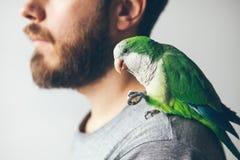 Bebouwde fotospruit van het profiel van baardmensen met zijn huisdier - groene papegaai royalty-vrije stock afbeeldingen