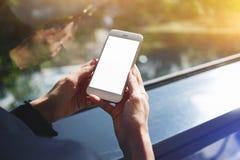 Bebouwde geschotene mening die van de handen van een vrouw mobiele telefoon met het lege exemplaar ruimtescherm houden voor uw te Stock Afbeelding