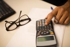 Bebouwde hand op bedrijfspersoon die calculator gebruiken door oogglazen op kantoor Stock Afbeeldingen