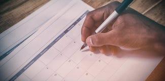 Bebouwde hand van zakenman die data op kalender merken Royalty-vrije Stock Afbeeldingen