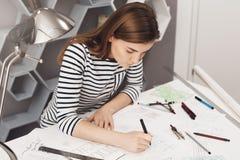 Bebouwde mening die van jonge uropean freelance ingenieur die niet formele gestreepte kleren dragen, bij lijst in coworking het o Stock Afbeeldingen