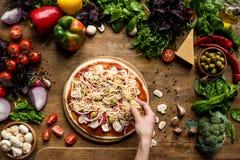 Bebouwde mening die van persoon eigengemaakte pizza met kaas en verse ingrediënten maken royalty-vrije stock foto's