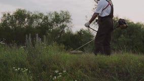 Bebouwde mening van mannelijke tuinman die elektrische snoeischaar met behulp van stock footage