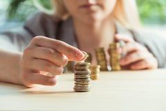 Bebouwde mening van vrouw die muntstukken op lijst stapelen royalty-vrije stock foto's