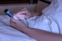 Bebouwde vrouw die op bed bij nacht liggen Mooi meisje die cellphone en het rusten gebruiken stock afbeeldingen
