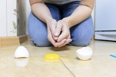 Bebouwde vrouwenzitting op een keukenvloer en klaar om gebroken ei met een weefsel uit keukenvloer te verwijderen stock fotografie